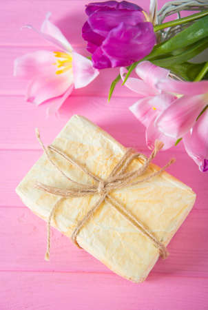 Crafted gift box and tender bouquet of beautiful pink tulips on pink wooden background. Mothers day present.
