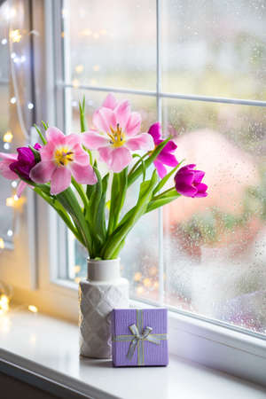 Gift box and tender bouquet of beautiful pink tulips in white vase near window with raindrops in the daylight. Spring blooming flowers with garland lights on background.