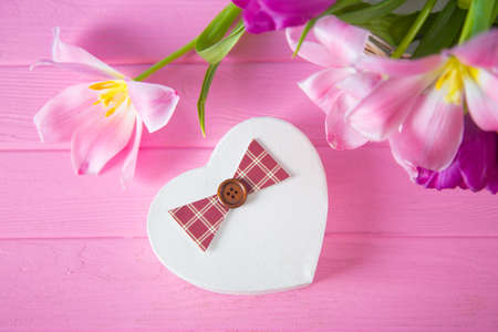 Gift box in shape of heart and tender bouquet of beautiful pink tulips on pink wooden background. Spring romantic present. Stock Photo