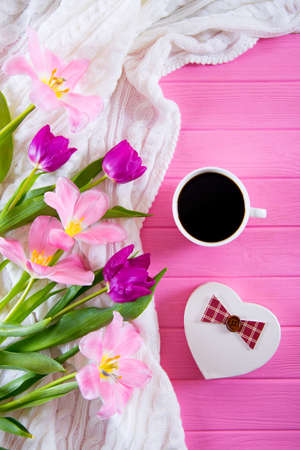 Cup of coffee, gift box in form of heart and tender bouquet of beautiful tulips on pink wooden background. Spring gift.