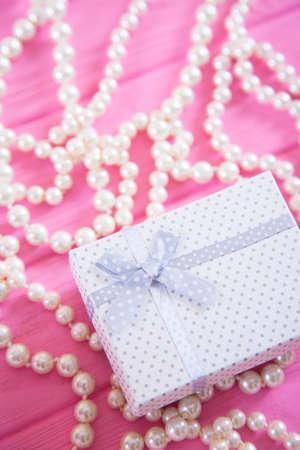 White gift box surrounded by pearl necklace on pink wooden background. Concept of Womens day gift.