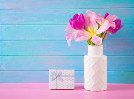 White gift box and tender bouquet of beautiful pink tulips in vase on blue and pink wooden background.
