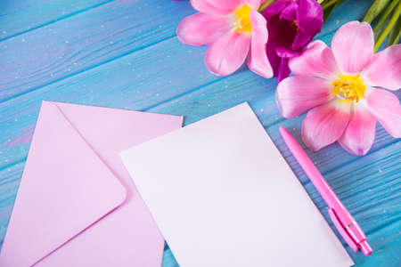 Clear sheet of white paper with pen and envelope and tender bouquet of beautiful tulips on creative blue wooden background. Spring greeting card with empty space.