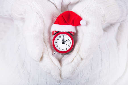 closeup hands in white knitted mittens holding red alarm clock in small santa hat new