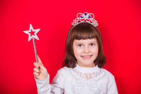 Cute smiling little girl in Christmas costume of fairy holding magic wand with star in studio on red background. New Year banner with empty space.