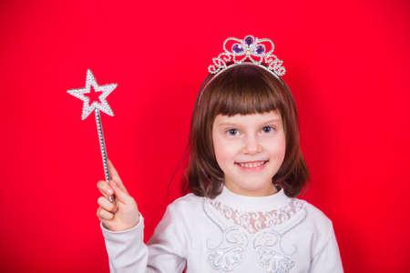 Linda niña sonriente en traje de Navidad de hadas con varita mágica con estrella en estudio sobre fondo rojo. Banner de año nuevo con espacio vacío. Foto de archivo