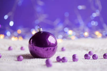 Purple Christmas ball and beads on white knitted fabric on purple background with warm bokeh. New year card. Xmas decoration.