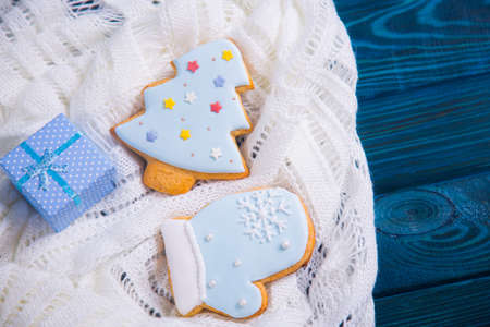 Christmas gingerbread decorated with icing and blue gift box on knitted white fabric. New Year homemade cookie.