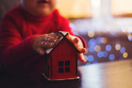 Children's hands holding Christmas toy red house with garland bokeh background indoor at home. Toddler boy plays with New Year decoration.