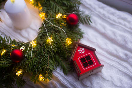Toy wooden winter house near fir wreath decorated with red Christmas balls, white candle and coiled with glowing garland with warm light on white knitted plaid. New Year home decoration Stock Photo