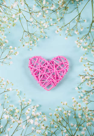 Pink wicker heart surrounded with white gypsophila flowers on mint blue background, top view. Spring romantic card.