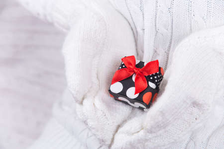 Hands in white knitted mittens holding pretty spotted gift box. Christmas present. New Year card. Foto de archivo