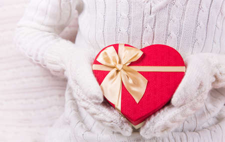 Hands in white knitted mittens holding gift box in shape of red heart. Valentine Day card. Romantic present Foto de archivo