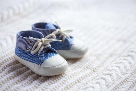 Cute baby boy blue sneakers on white knitted fabric. Concept of first shoes. Stockfoto