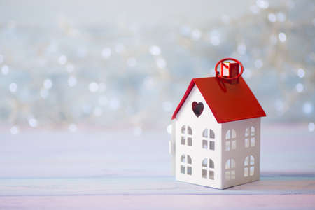 Toy white house with red roof and hole in form of heart on light bokeh background. Romantic card. Valentine day banner.
