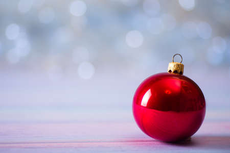 Red Christmas ball on light bokeh background. New Year festive card with copy space.