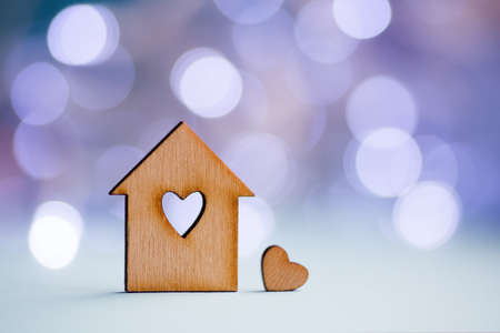 Wooden icon of house with hole in the form of heart with little heart on pastel blurred background with light bokeh. Romantic card with copy space. Concept of sweet home.