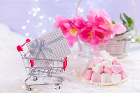 Small supermarket trolley with gift box and beautiful bouquet of tender pink tulips and marshmallow on blurred lilac background with bokeh. Concept of Womens day present. Spring shopping with copy space