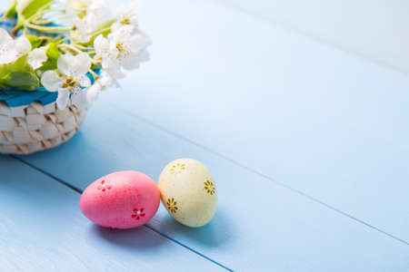 Two painted pink and yellow Easter eggs near basket with white spring flowering branch on light blue background. Banque d'images