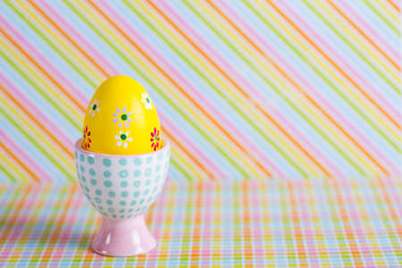 Closeup colorful painted Easter egg in vibrant modern egg stand on striped rainbow background. Spring home minimalistic composition with copy space. Geometric style.