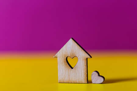Closeup wooden house with hole in form of heart on vibrant crimson and yellow background. Concept of sweet home, copy space