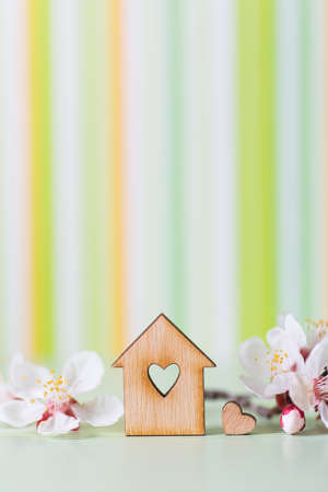 Closeup wooden house with hole in form of heart surrounded by white flowering tree branches on green striped background. Spring vibrant composition with copy space. Concept of sweet home. Archivio Fotografico