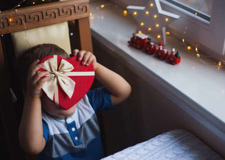 Little child boy hiding behind red heart shaped gift box with bow near window in daylight. Valentine day present. Surprise for beloved and dear person.