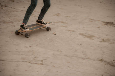 Legs on longboard in motion