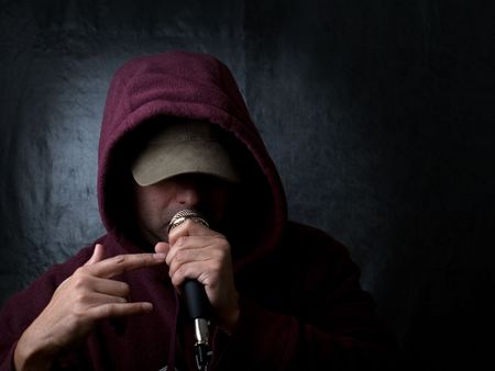 rapper wearing hood and singing to a microphone Stock Photo - 6782382