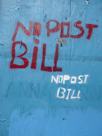 stenciled: Sign of no post bill on blue wall Stock Photo