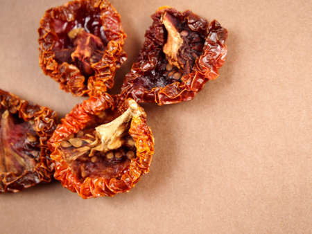 Dried tomatoes on brown background