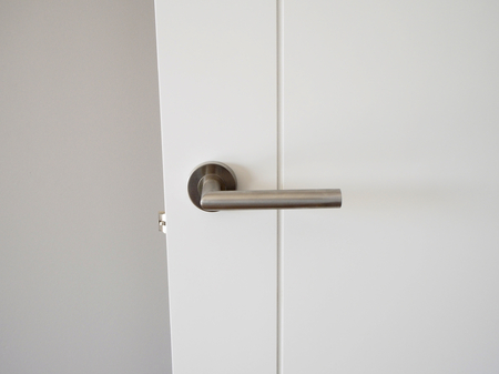 door handle: Metal handle in white door Stock Photo