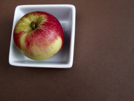 pome: Akane apple in a bowl on brown background