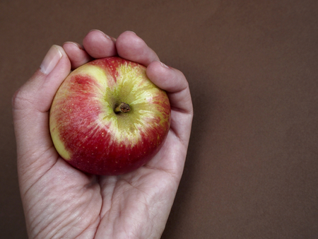 pome: Akane apple with hand on brown back ground