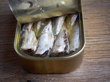 sardine can: Canned sardines on wood background