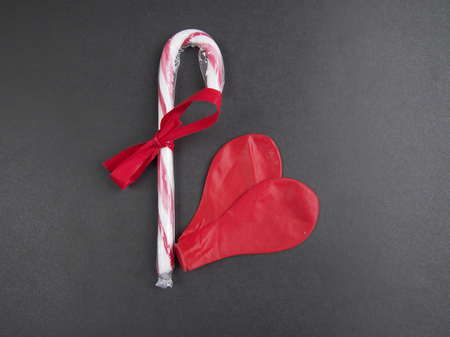deflated: Two deflated red balloon forming a heart with candy cane