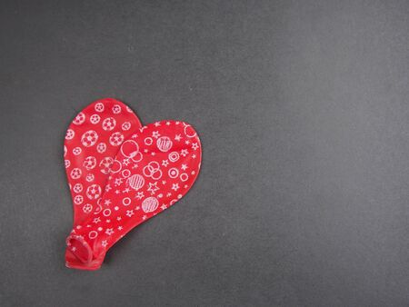 deflated: Two deflated red balloon forming a heart on black background