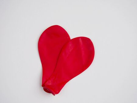deflated: Two deflated red balloon forming a heart on white background Stock Photo