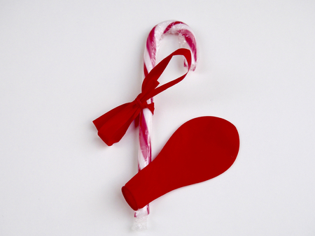 Red and white candy cane and red deflated balloon on white background