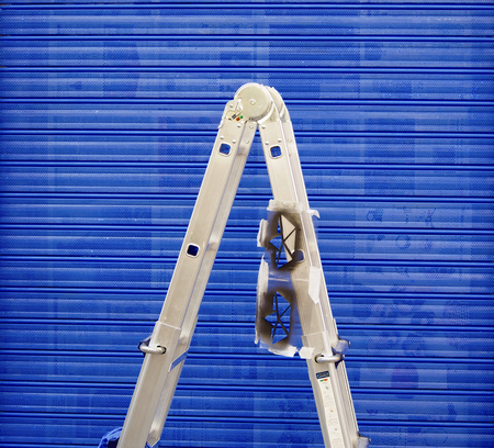 Aluminum ladder on blue background Stock Photo