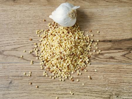 Raw fregola with garlic on wood background Stock Photo