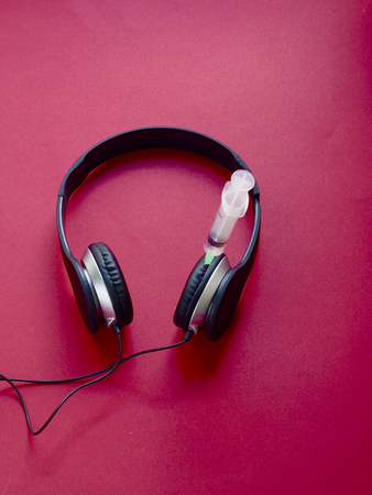 Headphone with syringe on red background - Addict to music concept