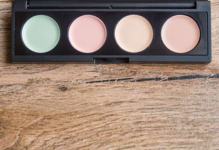 Palette with different makeup correctors on wood background Archivio Fotografico