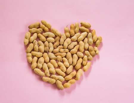 Peanuts forming a heart on pink background