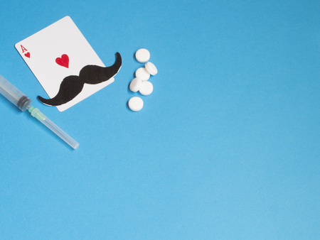 Mustache and ace hearts card and medicines on blue background