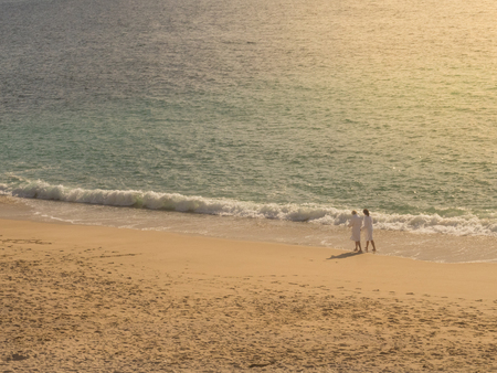 Couple walking on the beach with white bathrobe