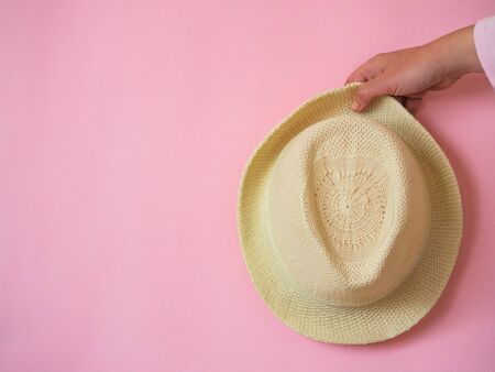 Hand holding hat on pink background with copy space
