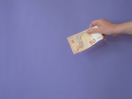 Hand with banknote of fifty euros on purple bankground with copy space