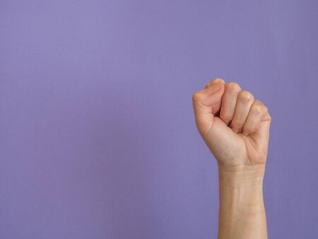 Hand with clenched fist on purple background with copy space