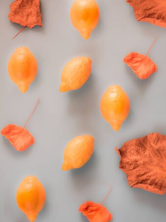 Orange lemons and fall leaves pattern on grey background Фото со стока